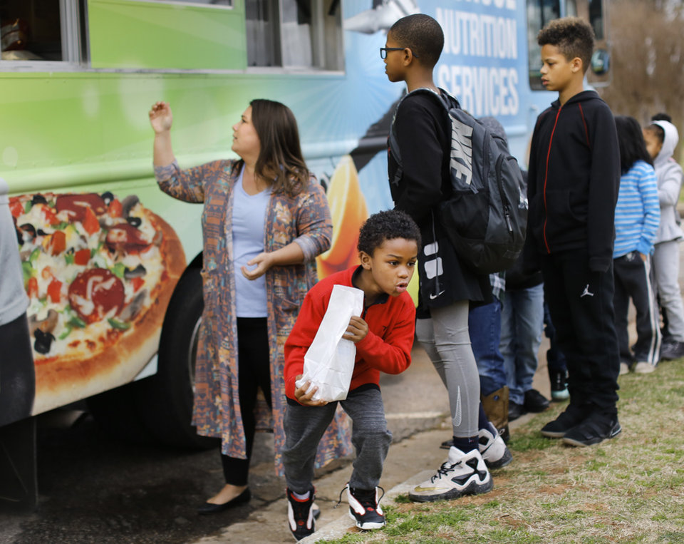 Photo - A young boy races back to the building after he and other students receive sack lunches from a food truck provided by Oklahoma City Public Schools Nutrition Services on Monday, April 2, 2018. As a result of the teacher walkout, children who spent their day at the Boys and Girls Club of Oklahoma County  received free lunches from the school district. Photo by Jim Beckel, The Oklahoman
