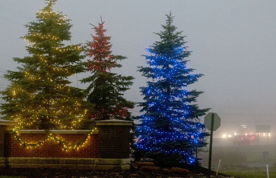 Christmas lights decorate trees at the East Beltline entrance for Cornerstone University as morning fog changes the landscape around Grand Rapids, Mich., Monday, Dec. 3, 2012. (AP Photo/The Grand Rapids Press, Chris Clark)