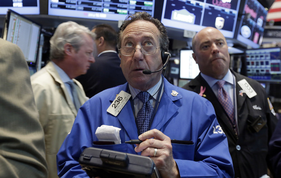 Photo - Trader Steven Kaplan, center, works on the floor of the New York Stock Exchange, Monday, Aug. 4, 2014. U.S. stocks are opening mostly higher as the market recovers from a two-day slide last week. (AP Photo/Richard Drew)