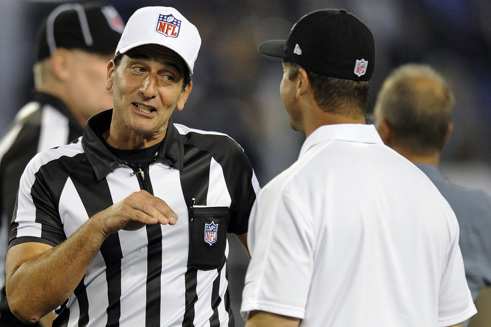 Photo -   Referee Gene Steratore, left, talks with Baltimore Ravens head coach John Harbaugh before an NFL football game between the Ravens and the Cleveland Browns in Baltimore, Thursday, Sept. 27, 2012. (AP Photo/Nick Wass)