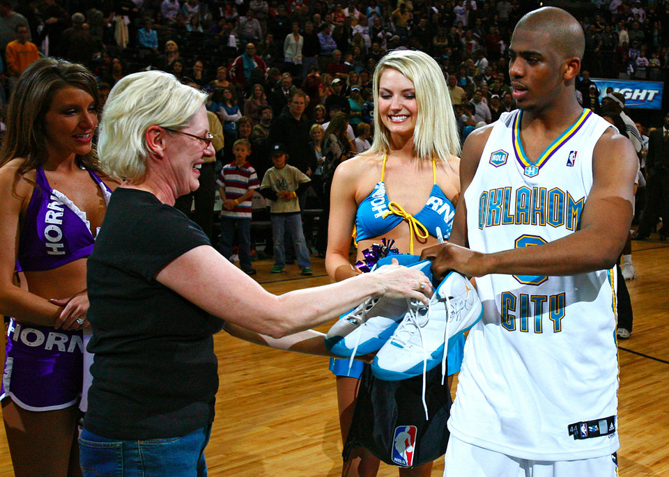 Photo - FAN: The Hornets' Chris Paul (3) give a pair of autographed shoes to Hornets season ticket holder Carol Barnes in the post game activites after the Hornets' 107-105 loss to Denver in the final regular season home game for the New Orleans/Oklahoma City Hornets and the Denver Nuggets NBA basketball game at the Ford Center on Friday, April 13, 2007, Oklahoma City, Okla.   staff photo by CHRIS LANDSBERGER ORG XMIT: KOD