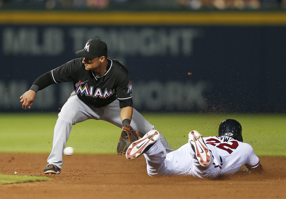 Photo - Atlanta Braves Jason Heyward steals second base as the ball gets away from Miami Marlins second baseman Donovan Solano (17) in the eighth inning of baseball game in Atlanta, Wednesday, July 23, 2014. (AP Photo)
