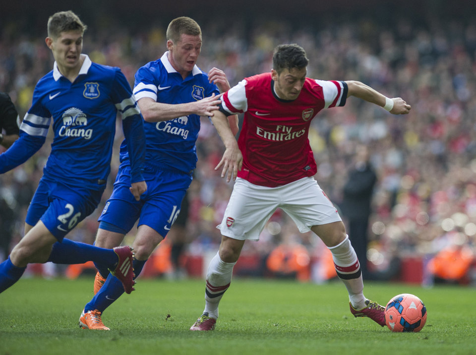 Photo - Arsenal's Mesut Özil, fights for the ball with Everton's John Stones and James McCarthy, during their FA Cup quarterfinal soccer match, at Emirates Stadium, in London, Saturday, March 8, 2014. (AP Photo/Bogdan Maran)