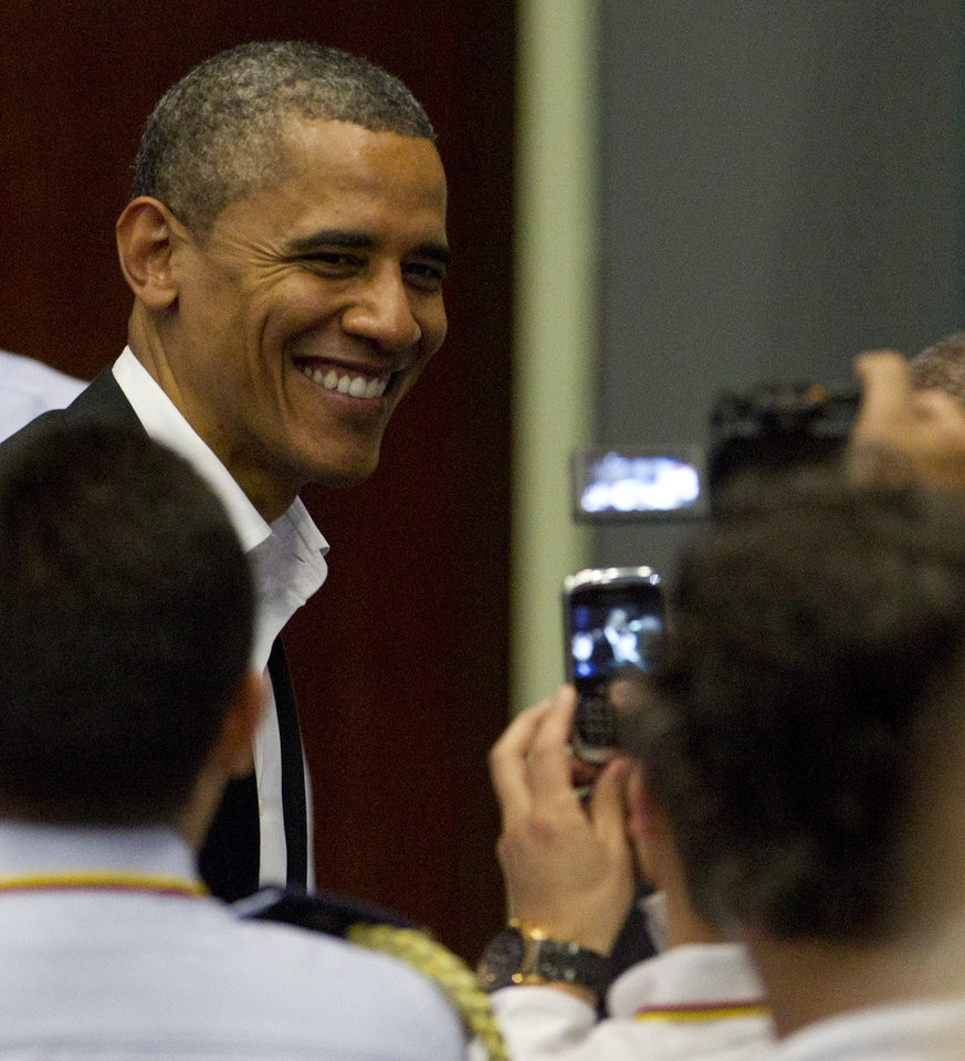 Photo -   President Barack Obama smiles to people in the audience taking his picture during the arrival ceremony at the sixth Summit of the Americas in Cartagena, Colombia, Saturday April 14, 2012. (AP Photo/Carolyn Kaster)