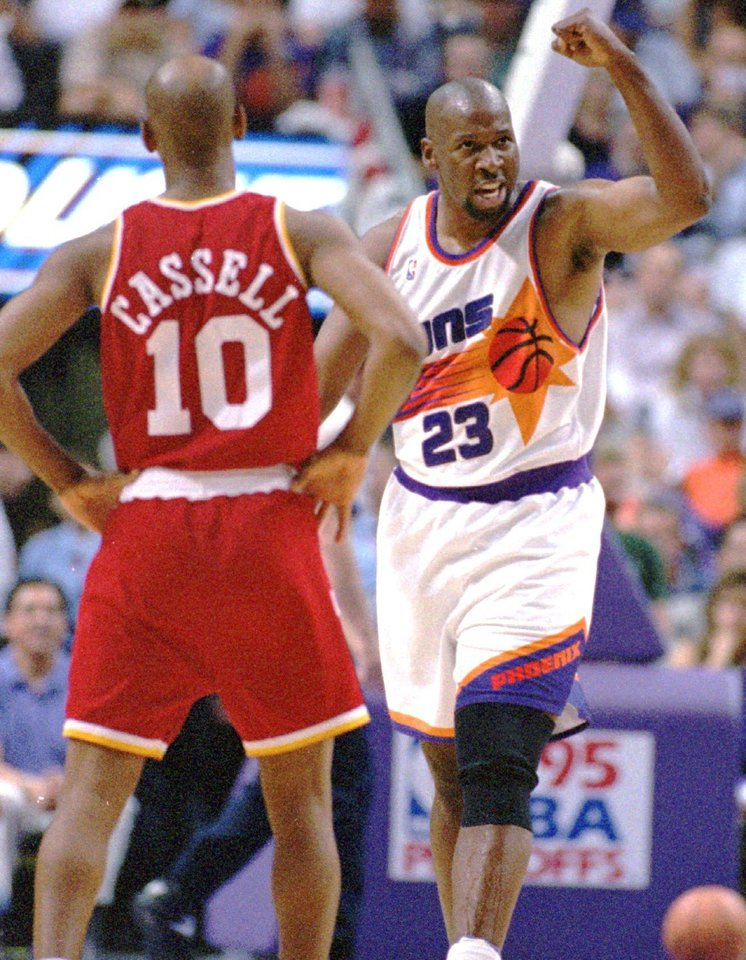 Photo - Phoenix Suns basketball forward Wayman Tisdale gestures after making a basket as he heads past Houston Rockets guard Sam Cassell in the second period of their NBA playoff game Thursday, May 11, 1995, in Phoenix. (AP Photo/Scott Troyanos)