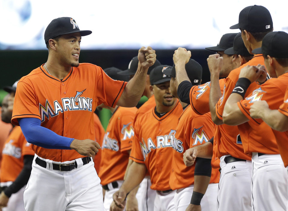 Photo - Miami Marlins right fielder Giancarlo Stanton, left, fist bumps his teammates before an opening day baseball game against the Colorado Rockies, Monday, March 31, 2014, in Miami. (AP Photo/Lynne Sladky)