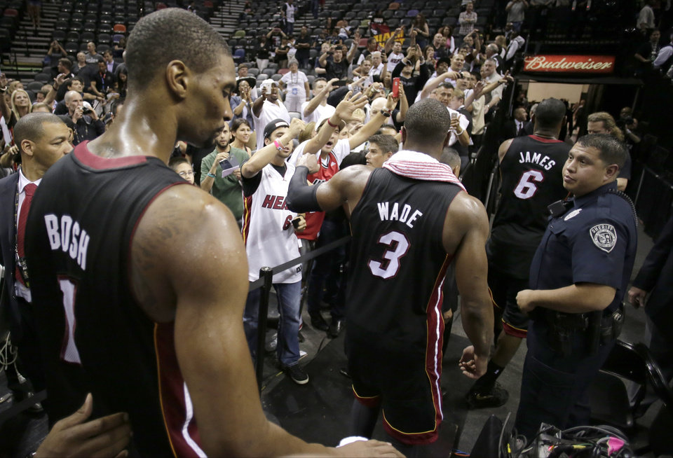 Photo - Miami Heat's Chris Bosh (1), Dwyane Wade (3), and LeBron James (6) leave the floor after defeating San Antonio Spurs at Game 4 of the NBA Finals basketball series, Thursday, June 13, 2013, in San Antonio. The Heat won 109-93. (AP Photo/Eric Gay)