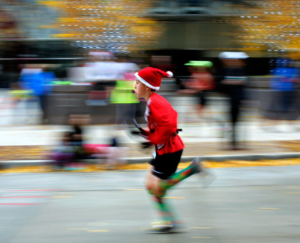 Photo -  A runner dressed in a Santa outfit nears the finish line of the 2015 SandRidge Santa Run. Many participants wore costumes and hats with a Christmas or Santa Claus theme. [Photo by Jim Beckel, The Oklahoman Archives]