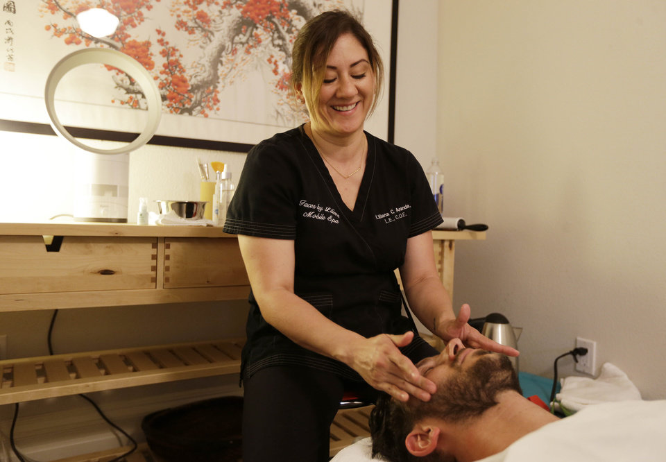 Photo - In this photo taken Tuesday, July 29, 2014, Liliana Aranda, owner of Faces by Liliana, does a peppermint neck and scalp treat to Dr. Austin Davis at his chiropractic office in San Francisco. Aranda's four-year-old company gives facials, massages and other spa treatments in homes or offices in the San Francisco area. (AP Photo/Eric Risberg)