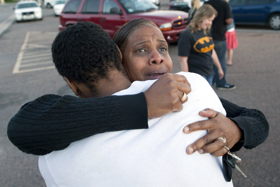 Photo - Shamecca Davis hugs her son Isaiah Bow, who was an eye witness to the shooting, outside Gateway High School where witness were brought for questioning Friday, July 20, 2012 in Denver.  After leaving the theater Bow went back in to find his girlfriend.