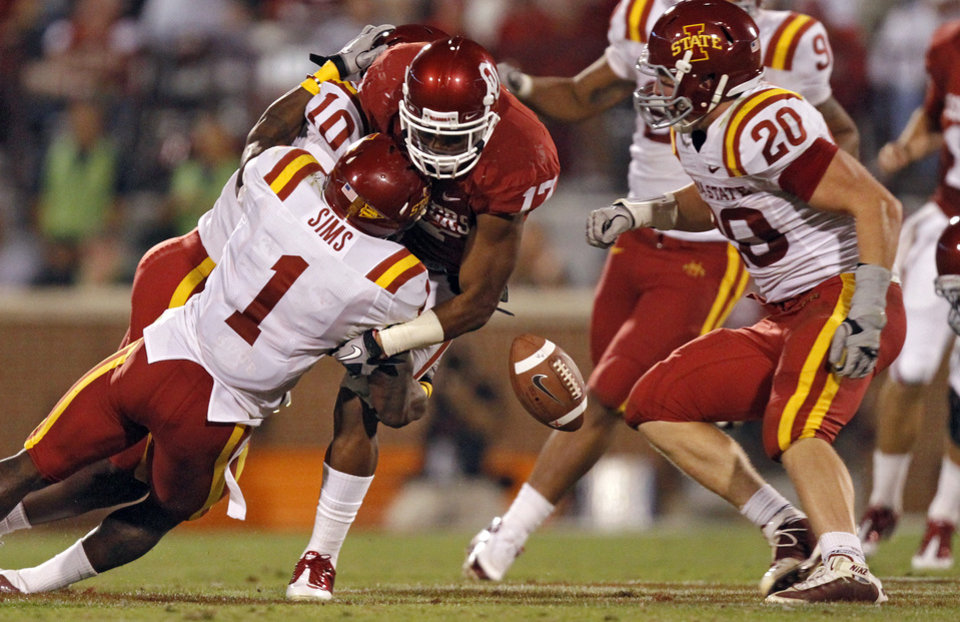 Photo - Oklahoma's Mossis Madu (17) fumbles the ball as he is hit by Iowa State's David Sims (1) during the second half of the college football game between the University of Oklahoma Sooners (OU) and the Iowa State Cyclones (ISU) at the Gaylord Family-Oklahoma Memorial Stadium on Saturday, Oct. 16, 2010, in Norman, Okla.  Photo by Chris Landsberger, The Oklahoman