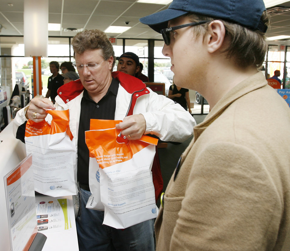 Photo - John E. Wolf III, left, collects his sacks containing his IPhone and accessories next to his son Blake Wolf after buying an iPhone during the debut of the iPhone in the AT&T store at 6959 NW Expressway in Oklahoma City, Friday, June 29, 2007. [THE OKLAHOMAN ARCHIVES]
