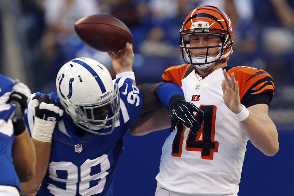 Photo -   Cincinnati Bengals quarterback Andy Dalton (14) is hit by Indianapolis Colts defensive end Robert Mathis in the first half of an NFL preseason football game in Indianapolis, Thursday, Aug. 30, 2012. Dalton left the game after the hit. (AP Photo/John Sommers II)