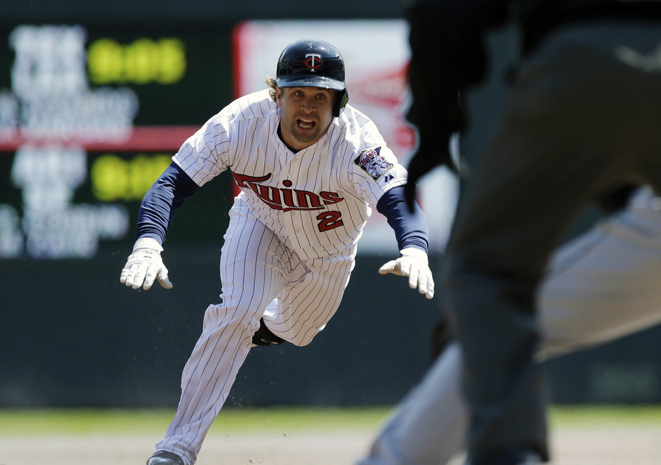 Photo - Minnesota Twins' Brian Dozier dives safely into third for a triple in the first inning off Miami Marlins pitcher Jose Fernandez in the first inning of a baseball game Tuesday, April 23, 2013 in Minneapolis, Minn. (AP Photo/Jim Mone)