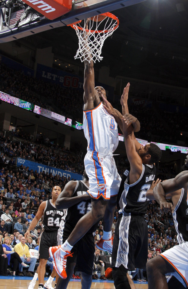 Photo - Oklahoma City Thunder's Serge Ibaka (9) shoots over San Antonio Spurs' Tim Duncan (21) during the the NBA basketball game between the Oklahoma City Thunder and the San Antonio Spurs at the Chesapeake Energy Arena in Oklahoma City, Sunday, Jan. 8, 2012. Photo by Sarah Phipps, The Oklahoman