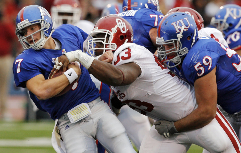Photo - OU's Gerald McCoy (93) tackles Kale Pick (7) of Kansas for a loss in front of KU's Sal Capra (59) during the second half of the college football game between the University of Oklahoma Sooners (OU) and the University of Kansas Jayhawks (KU) on Saturday, Oct. 24, 2009, in Lawrence, Kan. OU won, 35-13. Photo by Nate Billings, The Oklahoman