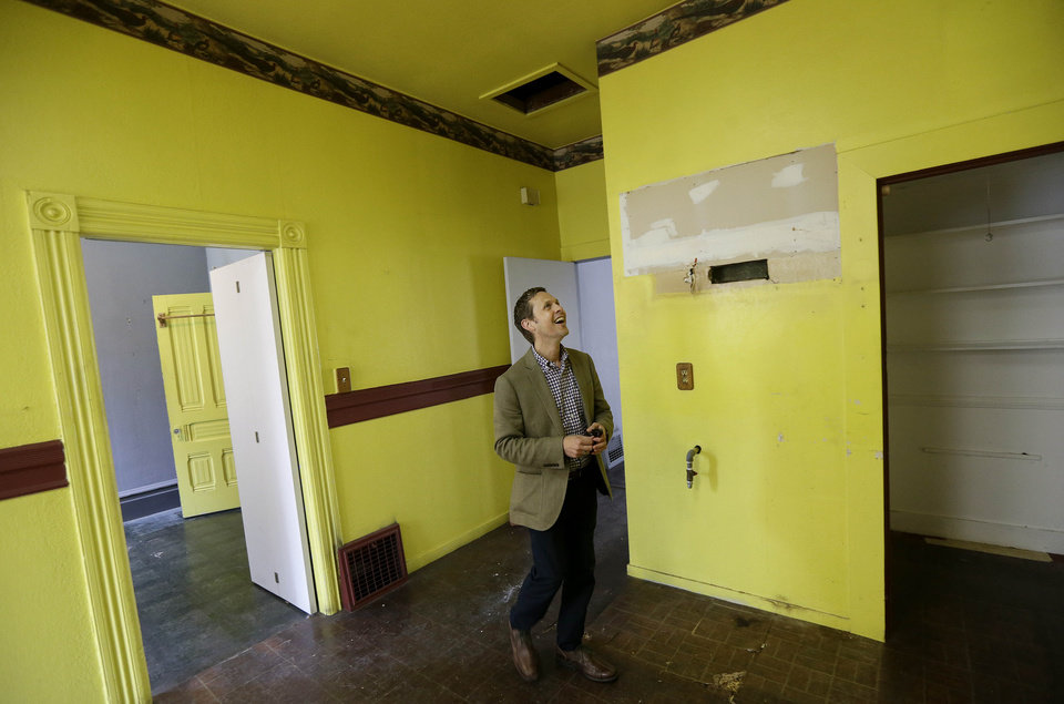 Photo - George Limperis, a realtor with Paragon Real Estate Group, smiles as he walks through the kitchen of a property that was recently sold in the Noe Valley neighborhood in San Francisco, Wednesday, July 30, 2014. (AP Photo/Jeff Chiu)