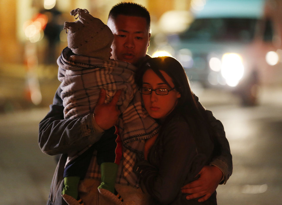 Photo - Johnny Nhatavong, center, of New Haven, Conn., embraces his wife, Melennie Rizek, right, and their 11-month-old son Kenzo Jung while stopping at a makeshift memorial near the place where a day earlier a gunman opened fire inside of an elementary school, Saturday, Dec. 15, 2012, in Newtown, Conn. The man, who died from a self-inflicted wound, allegedly killed his mother at their home and then opened fire Friday inside the Sandy Hook Elementary school, massacring 26 people, including 20 children. (AP Photo/Julio Cortez) ORG XMIT: CTJC139