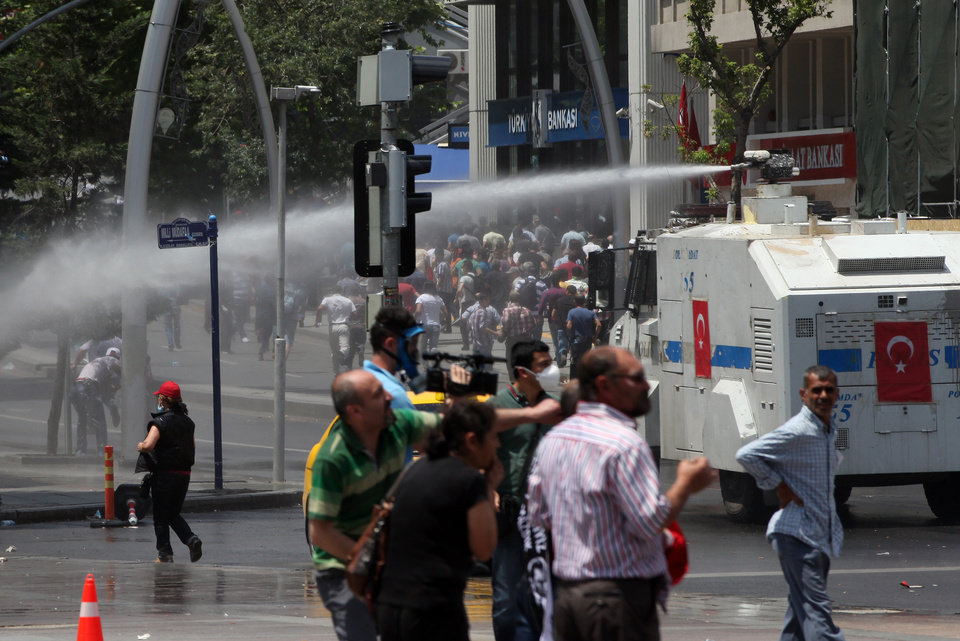 Photo - Turkish riot police spray water cannon at demonstrators who remained defiant after authorities evicted activists from an Istanbul park, making clear they are taking a hardline against attempts to rekindle protests that have shaken the country, in city's main Kizilay Square in Ankara, Turkey, Sunday, June 16, 2013. (AP Photo/Burhan Ozbilici)