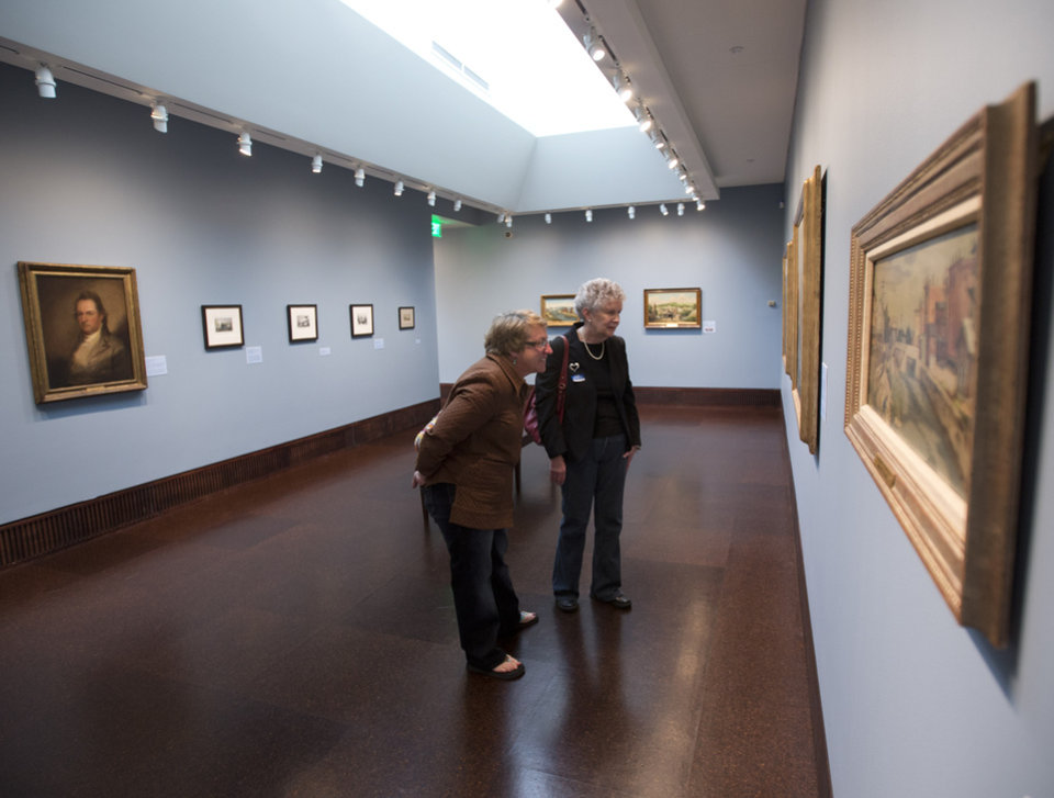 Photo - This May 2, 2014 photo shows Meredith Lord, left, and Louise Darragh, both of Johnstown, N.Y., viewing paintings of the Mohawk River at the Arkell Museum in Canajoharie, N.Y. The museum, started in 1928 by Bartlett Arkell, founder of the Beech-Nut food company, is located next door to company's former plant in Canajoharie, population 2,200. (AP Photo/Mike Groll)