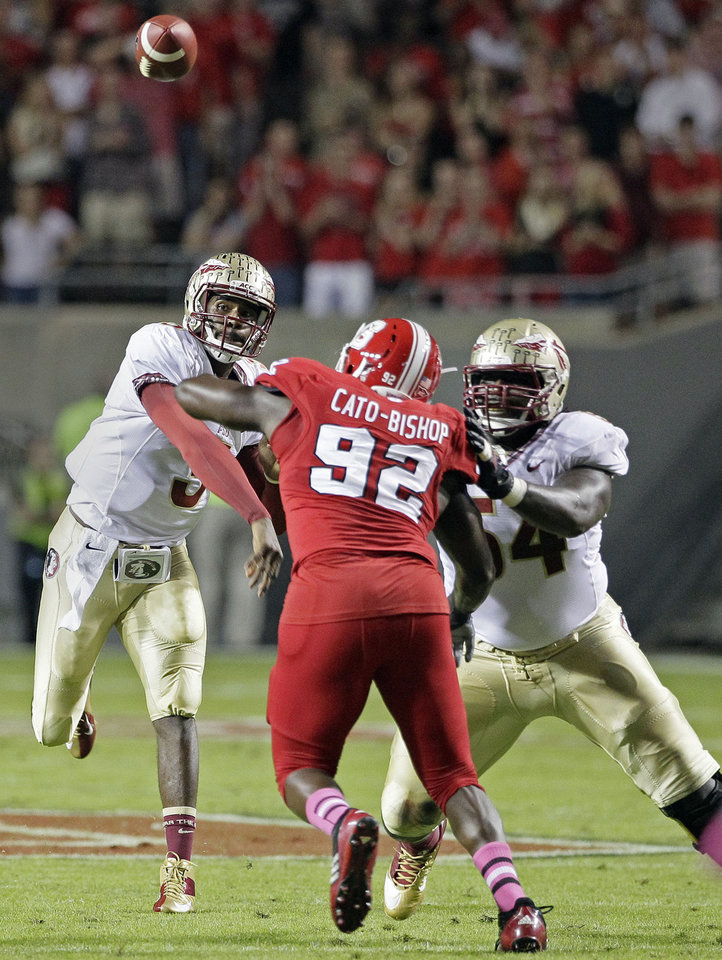 Florida State quarterback EJ Manuel passes as Tre' Jackson (54) blocks North Carolina State's Darryl Cato-Bishop (92) during the first half of an NCAA college football game in Raleigh, N.C., Saturday, Oct. 6, 2012. (AP Photo/Gerry Broome)