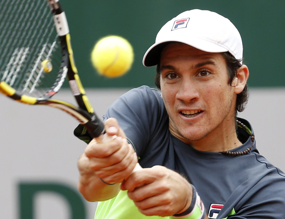Photo - Argentina's Facundo Bagnis returns the ball to Latvia's Ernests Gulbis during their second round match of  the French Open tennis tournament at the Roland Garros stadium, in Paris, France, Wednesday, May 28, 2014. (AP Photo/Darko Vojinovic)