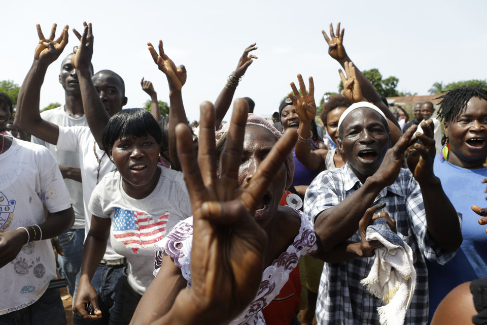 Photo -   Supporters of incumbent President Ernest Bai Koroma cheer and hold up four fingers to show they want the ruling party to sweep the elections, as Koroma leaves after voting, in Freetown, Sierra Leone, Saturday, Nov. 17, 2012. A decade after Sierra Leone's brutal civil war, voters on Saturday chose between an incumbent president who has provided new roads and free health care and a field of opposition candidates who decry the poverty and pace of economic recovery.(AP Photo/Rebecca Blackwell)