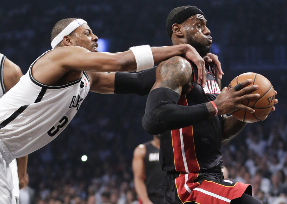 Photo - Brooklyn Nets forward Paul Pierce (34) fouls Miami Heat forward LeBron James (6) as he drives through the lane to score in the first period during Game 3 of an Eastern Conference semifinal NBA playoff basketball game on Saturday, May 10, 2014, in New York. Pierce was called for a flagrant foul and James scored on the play. (AP Photo/Julie Jacobson)
