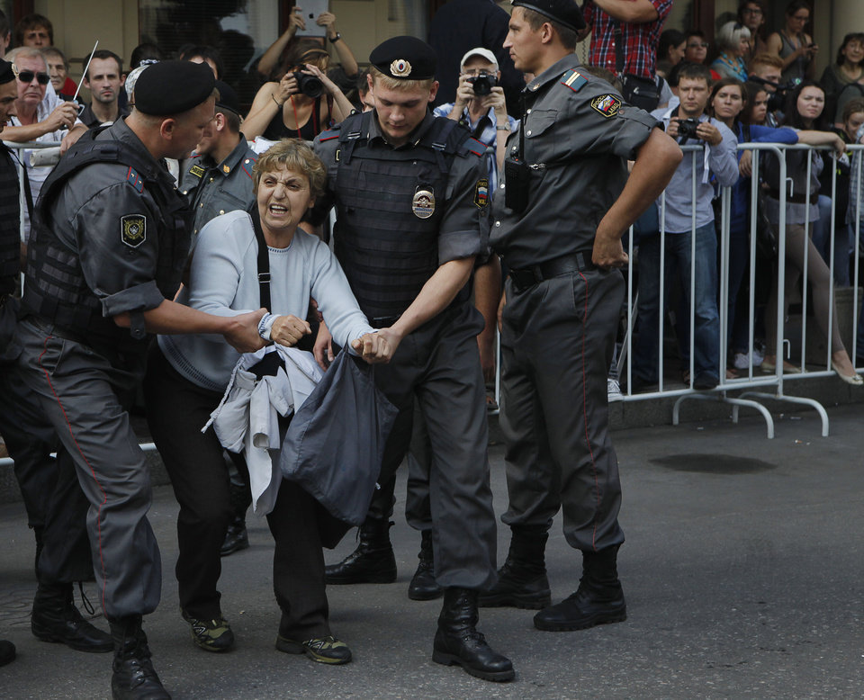 Photo -   Police officers detain a supporter of the Russian punk group Pussy Riot outside a court in Moscow, Russia, Friday, Aug. 17, 2012. A Moscow judge has sentenced each of three members of the provocative punk band Pussy Riot to two years in prison on hooliganism charges following a trial that has drawn international outrage as an emblem of Russia's intolerance to dissent. (AP Photo/Alexander Zemlianichenko)