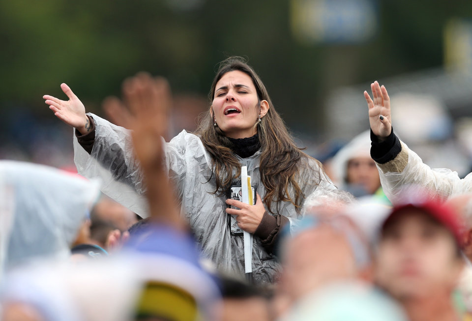 Photo - A woman prays during a Mass celebrated by Pope Francis outside the Aparecida Basilica in Aparecida, Brazil, Wednesday, July 24, 2013. Tens of thousands of faithful flocked to the tiny town of Aparecida, tucked into an agricultural region halfway between Rio de Janeiro and Sao Paulo, where he is to celebrate the first public Mass of his trip in a massive basilica dedicated to the nation's patron saint. (AP Photo/Andre Penner)