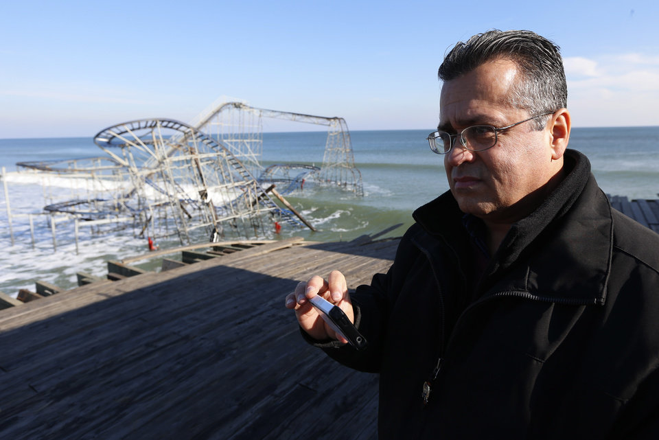 New Jersey State Assemblyman Angel Fuentes stands on the Funtown Pier at Seaside Heights as a roller coaster is dunked in the ocean during a tour of the areas hit by Superstorm Sandy, Thursday, Nov. 29, 2012, in Seaside Heights, N.J. (AP Photo/Julio Cortez)