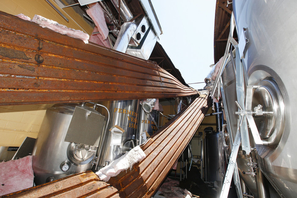 Fermentation vessels sit beneath the collapsed roof at the OKCity Brewing Cooperative near downtown Oklahoma City. The building was heavily damaged by the May 31 storms. PHOTO BY PAUL B. SOUTHERLAND, THE OKLAHOMAN <strong>PAUL B. SOUTHERLAND</strong>