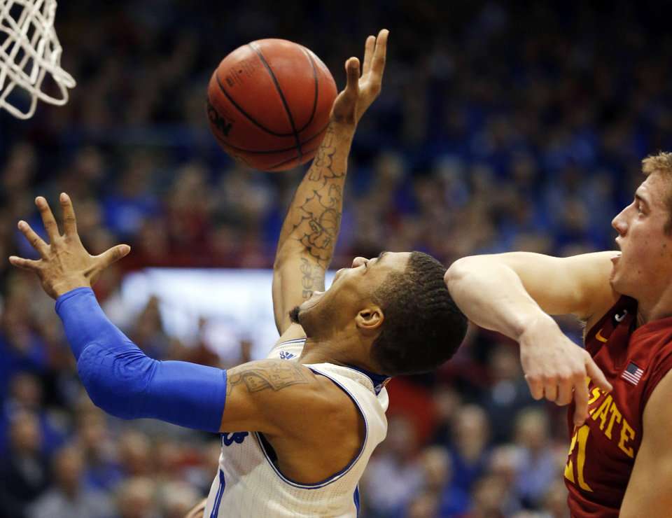 Photo - Iowa State guard Matt Thomas, right, blocks a shot by Kansas guard Frank Mason, left, during the first half of an NCAA college basketball game in Lawrence, Kan., Wednesday, Jan. 29, 2014. (AP Photo/Orlin Wagner)