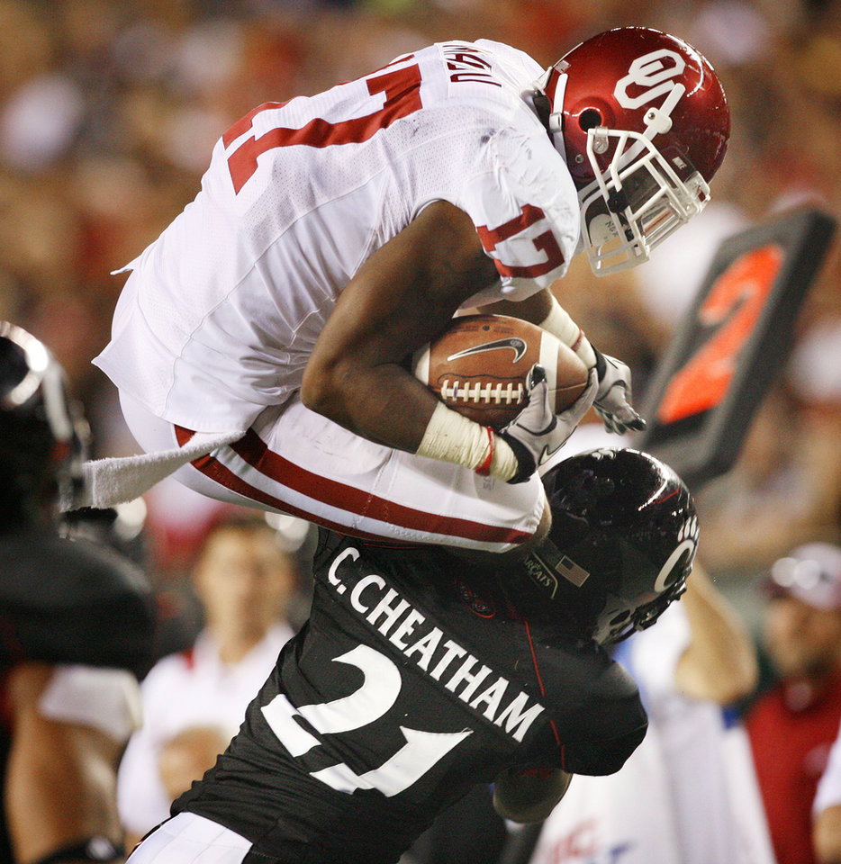 Mossis Madu (17) leaps over Camerron Cheatham (22) during the second half of the college football game between the University of Oklahoma Sooners (OU) and the University of Cincinnati Bearcats (UC) at Paul Brown Stadium on Saturday, Sept. 25, 2010, in Cincinnati, Ohio.   Photo by Steve Sisney, The Oklahoman ORG XMIT: KOD