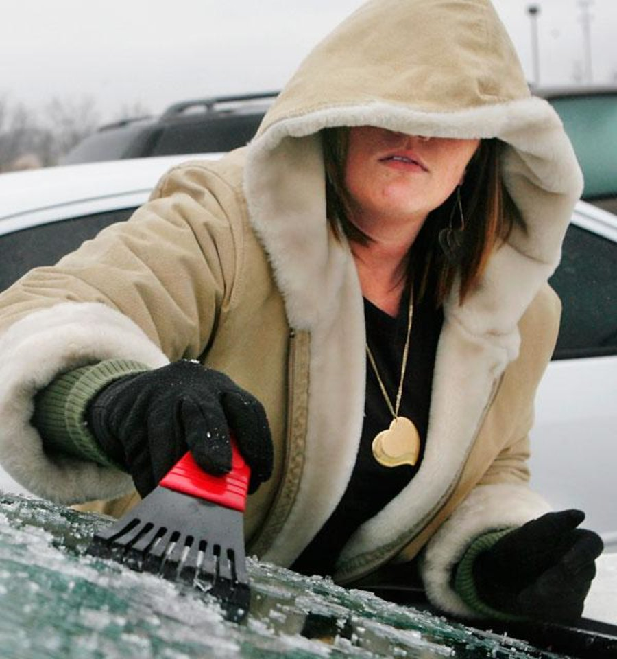 Photo -  Nikole Edwards scrapes ice from her car windows after she and other employees at Farmer's Insurance  at NW 23 and Villa were released early because of deteriorating weather conditions Monday, Jan. 26, 2009.  BY JIM BECKEL, THE OKLAHOMAN