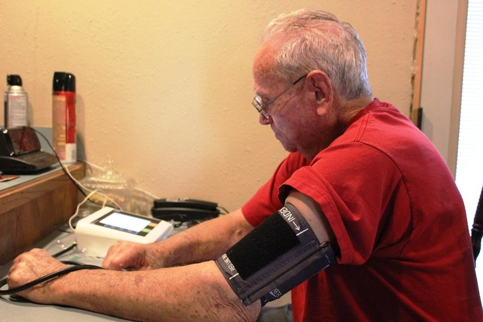 Photo -  Wesley Ercanbrack, 84, checks his blood pressure using a telemedicine device in his home. He and his wife, Billie Jean, are patients in an Oklahoma City physician house call service. Photo Provided    Provided  -  Provided