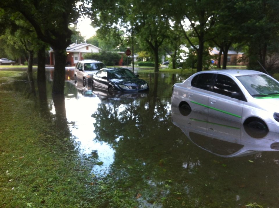 These cars were parked on NW 40 and were caught in flooding just west of N MacArthur Blvd in Warr Acres Wednesday. Photo by Robert Medley
