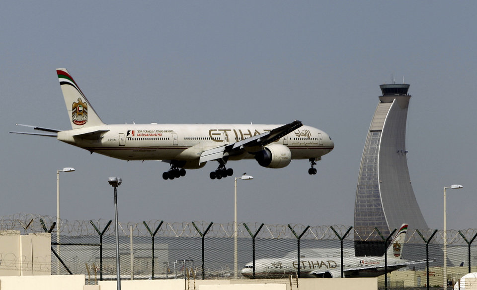 Photo - An Etihad Airways plan prepares to land at the Abu Dhabi airport, in United Arab Emirates, Sunday, May 4, 2014. Etihad Airways, a fast-growing Mideast carrier, laid out plans Sunday to offer passengers who find first-class seats a bit too tight a miniature suite featuring a closed-off bedroom, private bathroom and a dedicated butler. (AP Photo/Kamran Jebreili)