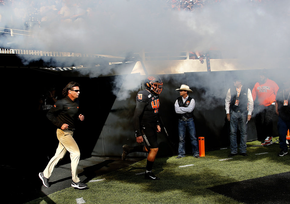 Photo - Oklahoma State head coach Mike Gundy runs onto the field before the college football game between the Oklahoma State University Cowboys and the TCU Horned Frogs at Boone Pickens Stadium in Stillwater, Okla.,  Saturday, Nov. 2, 2019. OSU won 34-27. [Sarah Phipps/The Oklahoman]