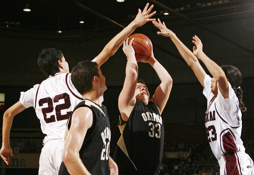 Photo - Okemah's Jeremy Baker (33) shoots between the defense of Kialo Vann (22) and Cody Fourkiller (23) of Sequoyah-Tahlequah as Jake Clark (20) looks on during the 3A boys semifinal game between Okemah and Sequoyah-Tahlequah in the Oklahoma High School Basketball Championships at State Fair Arena in Oklahoma City, Friday, March 13, 2009. Okemah won to advance to the finals. PHOTO BY NATE BILLINGS, THE OKLAHOMAN
