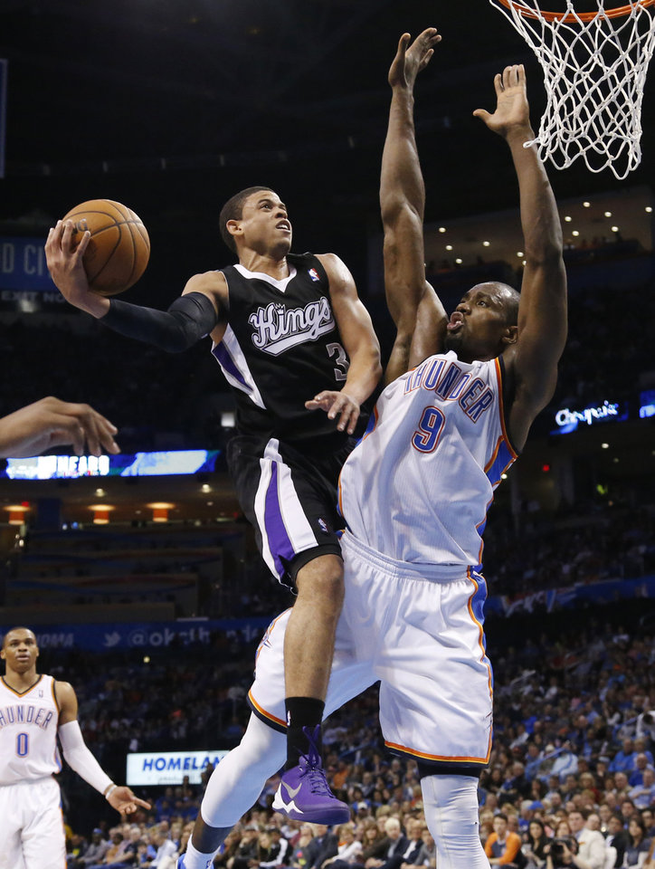 Photo - Sacramento Kings guard Ray McCallum (3) goes up for a shot in front of Oklahoma City Thunder forward Serge Ibaka (9) during the second quarter of an NBA basketball game in Oklahoma City, Friday, March 28, 2014. (AP Photo/Sue Ogrocki)
