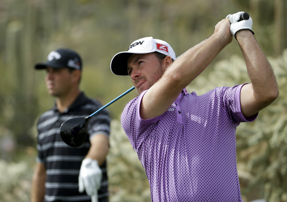 Photo - Graeme McDowell, right, of Northern Ireland, watches his tee shot on the 17th hole in his match against Gary Woodland during the first round of the Match Play Championship golf tournament on Wednesday, Feb. 19, 2014, in Marana, Ariz. (AP Photo/Ted S. Warren)
