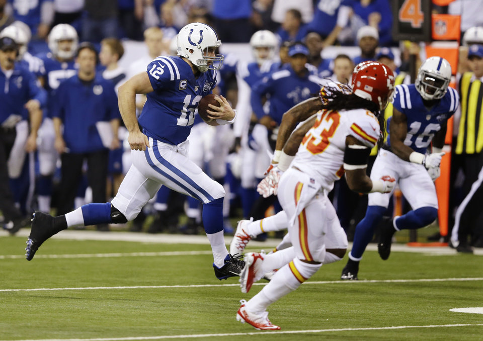 Photo - Indianapolis Colts' Andrew Luck (12) runs during the first half of an NFL wild-card playoff football game against the Kansas City Chiefs Saturday, Jan. 4, 2014, in Indianapolis. (AP Photo/Michael Conroy)