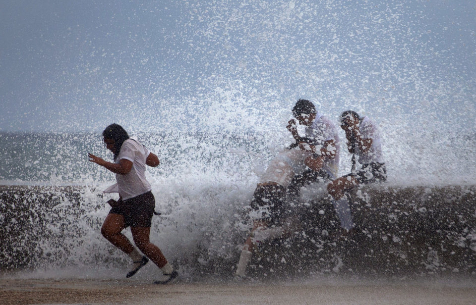 Photo -   Students play in the waves crashing against the Malecon after the passing of Hurricane Sandy in Havana, Cuba, Thursday, Oct. 25, 2012. Hurricane Sandy blasted across eastern Cuba on Thursday as a potent Category 2 storm and headed for the Bahamas after causing at least two deaths in the Caribbean. (AP Photo/Ramon Espinosa)