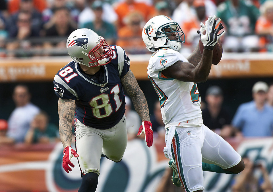 Photo - Miami Dolphins' Reshad Jones, right, intercepts the ball thrown to New England Patriots' Aaron Hernandez in the first quarter of their NFL football game, Sunday, Dec. 2, 2012, in Miami Gardens, Fla. The Patriots won 23-16 to clinch their fourth consecutive AFC East title. (AP Photo/The Miami Herald, C.W. Griffin) MAGS OUT.