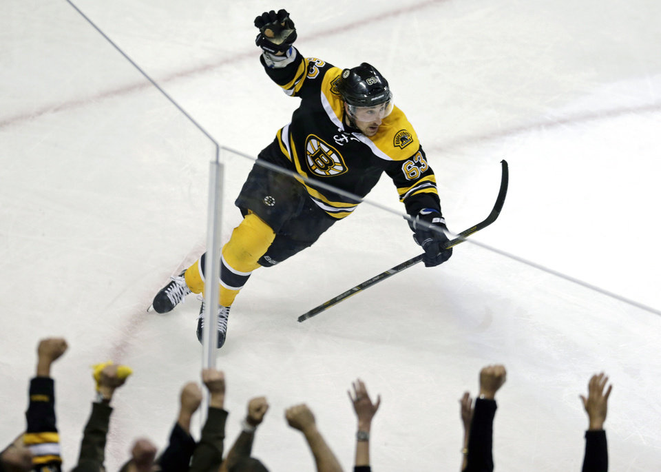 Photo - Boston Bruins left wing Brad Marchand celebrates following his game-winning goal against New York Rangers goalie Henrik Lundqvist during overtime in Game 1 of an NHL hockey playoffs Eastern Conference semifinal game in Boston, Thursday, May 16, 2013. The Bruins won 3-2. (AP Photo/Charles Krupa)