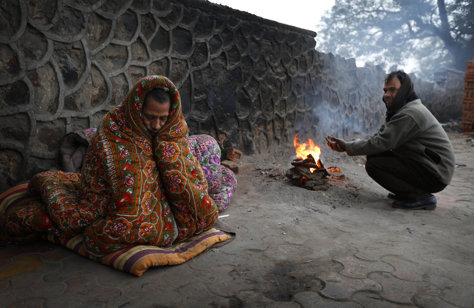 A man warms himself by a fire as another wraps himself up with a blanket to keep out the cold in New Delhi, India , Tuesday, Jan. 8, 2013. North India continues to face below average weather conditions with dense fog affecting flights and trains. More than 100 people have died of exposure as northern India deals with historically cold temperatures. (AP Photo/Saurabh Das)