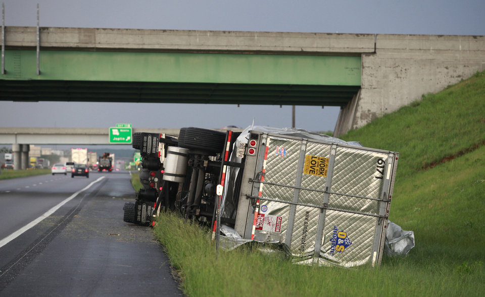 Photo - A tractor trailer is tipped over on Interstate 44 near Joplin, Mo., after the town was hit by a tornado on Sunday, May 22, 2011. (AP Photo/The Wichita Eagle, Jaime Green) ORG XMIT: KSWIE104