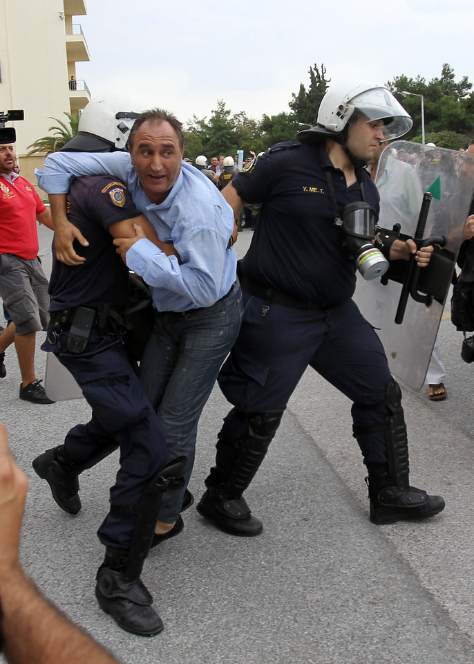 Riot police arrest a protester inside Greece's Defense Ministry in Athens, Thursday, Oct. 4, 2012. Police clashed with scores of protesting shipyard workers after they forced their way into the grounds of Greece's Defense Ministry. The workers say they have not been paid in months. (AP Photo/Thanassis Stavrakis)