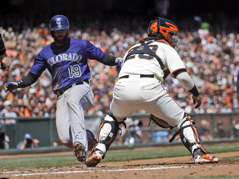 Photo - Colorado Rockies' Charlie Blackmon (19) scores past San Francisco Giants catcher Hector Sanchez, right, on a sacrifice fly hit by Troy Tulowitzki during the third inning of a baseball game on Saturday, April 12, 2014, in San Francisco. (AP Photo/Marcio Jose Sanchez)